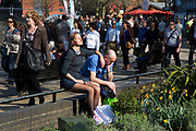 Woman enjoying the sun, lost in her own calm world as the crowds of people walk along on a Spring day. The South Bank is a significant arts and entertainment district, and home to an endless list of activities for Londoners, visitors and tourists alike.