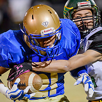 Zuni Thunderbird Jayden Sosseah (21) is tackled by Newcomb Skyhawk Adrian Yazzie (4) Friday at Zuni High School.