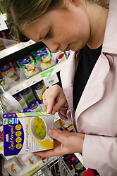 Woman checking food facts on packet soup,