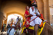 Parading on the backs of camels, Rajasthani men and women in traditional costumes at the Desert Festival on 29th January2018  in Jaisalmer, Rajasthan, India. It is an annual event that take place in February month in the beautiful city Jaisalmer. It is held in the Hindu month of Magh February, three days prior to the full moon. The men flaunt their moustaches, which go well with the Rajputana spirit that symbolizes the valor and glory of Rajasthan.