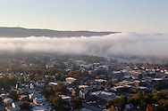 Port Jervis, N.Y. - Parts of Port Jervis are covered by early-morning fog on Oct. 14, 2006. The High Point Monument in New Jersey is visible on the top of the ridge at left. The monument marks the highest spot in the state. ©Tom Bushey