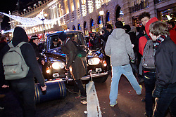 © under license to London News Pictures. 09/12/2010.  A mob surrounds the Royal Convoy carrying Prince Charles in Regent Street after it is accidentally driven into the middle of a riot. A rioter physically attacks his wife Camilla, Duchess of Cornwall, through an open window. The Rolls Royce carrying the couple is splattered with paint and a window is smashed. Photo credit should read Cliff Hide/LNP.