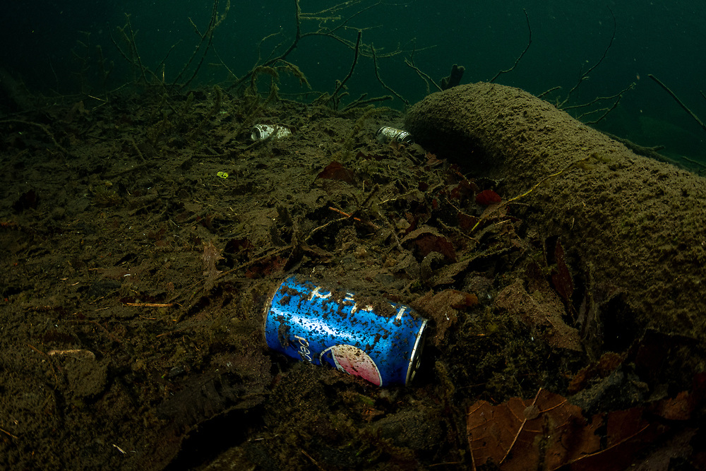 Pepsi cans litter a river on Vancouver Island, BC, Canada.