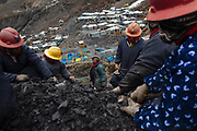 A women group works outside of a gold mine looking for gold into rock fragments that were extracted from the mine tunnels.