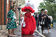 Racegoer Debra Day arrives wearing a red dress and a large red hat featuring a white swan on Ladies Day at Royal Ascot on 17th June 2021 in Ascot, United Kingdom. Despite Covid restrictions and changeable weather including some rain, many racegoers displayed the elaborate hats and fascinators for which Gold Cup Day has become well known.