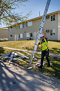 18 AUGUST 2020 - CEDAR RAPIDS, IOWA: A worker takes a ladder back to his pickup truck after working in a destroyed apartment complex in Cedar Rapids. Cedar Rapids was the state's hardest hit city by the derecho that roared across Iowa last week. City officials said the damage left by the derecho was more extensive than the 2008 flood that destroyed much of its downtown. City residents are reporting that almost every home was damaged in the storm, many businesses were closed, and up to half of the city's tree canopy was destroyed. A week after the storm, more than 40,000 homes were still without power. A spokesman for Alliant Energy said the utility has replaced as many power poles in one week that they normally replace in 8 months. On Monday, President Trump approved a $4 billion emergency declaration for Iowa to aid in derecho recovery.  PHOTO BY JACK KURTZ