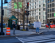 Washington, DC, USA — February 3, 2020. A man holding a protest sign stands on a street corner in Washington, DC.