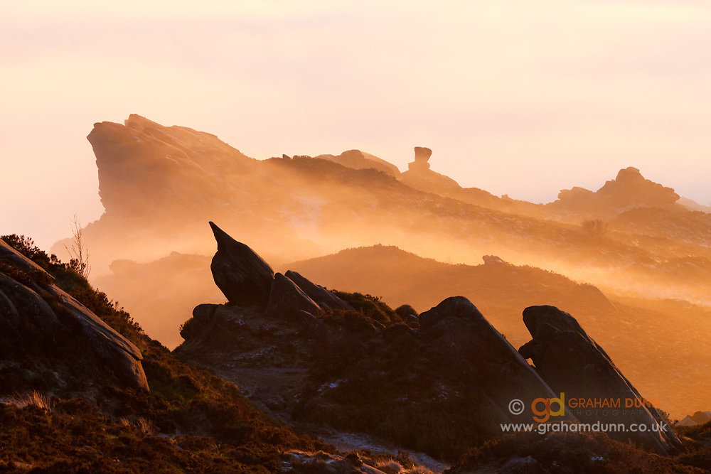Mist, illuminated by warm sunset light, glows amidst layers of rock on Ramshaw Rocks in the south-Western Peak District. A stunning temperature inversion in Staffordshire, England, UK.