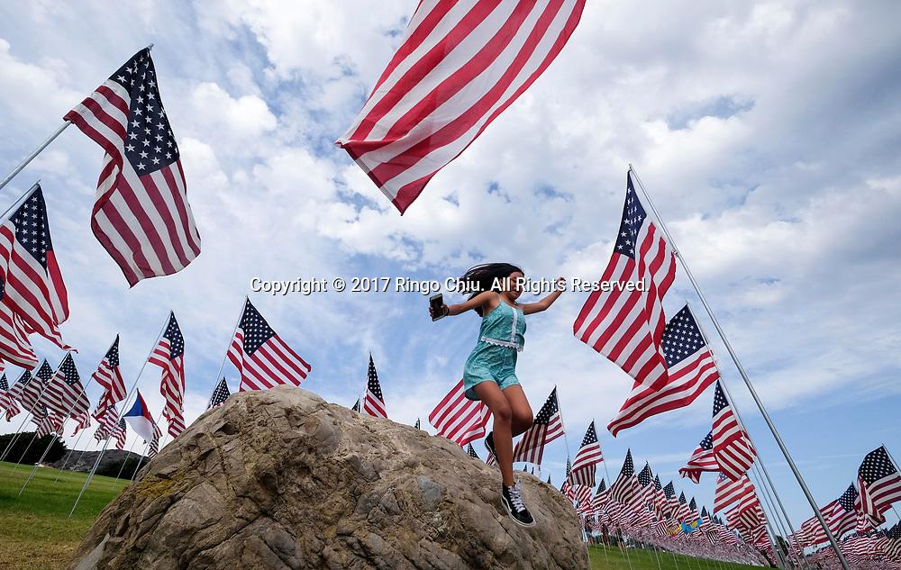"""9月10日,在美国加利福尼亚州洛杉矶的马里布,一名女孩在旗帜中间的石头上跳下。当天,在美国""""9·11""""事件十六周年前夕,佩珀代因大学的学生和教职员工在学校草坪上插起约3000面美国国旗,纪念""""9·11""""事件遇难者。新华社发(赵汉荣摄)<br /> A girl jumps from a rock amongst 3,000 of US national flags at a memorial honoring the victims of the Sept. 11, 2001 terrorist attacks, set by students and staff on the campus lawn of  Pepperdine University in Malibu, California, the United States, on Sunday, Sept. 10, 2017. (Xinhua/Zhao Hanrong)(Photo by Ringo Chiu)<br /> <br /> Usage Notes: This content is intended for editorial use only. For other uses, additional clearances may be required."""