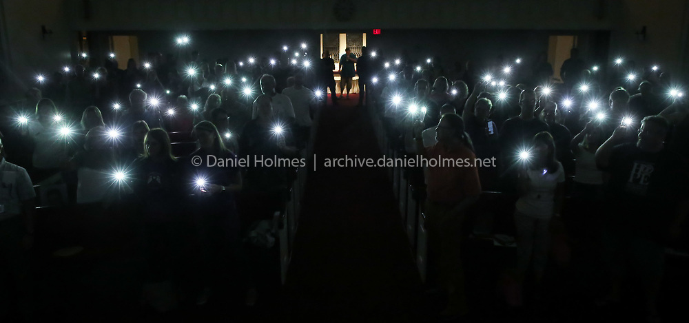 (8/28/19, MARLBOROUGH, MA) Participants hold up cell phone lights in place of candles during Opioid Awareness Day at First Church in Marlborough on Wednesday. [Daily News and Wicked Local Photo/Dan Holmes]