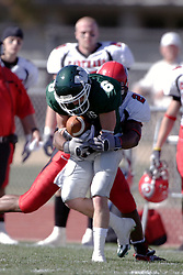 07 October 2006: Marcus Dunlap squeezes the ball tight to avoid a fumble while pressure is applied by a Red Man defender. The Titans of Illinois Wesleyan University started off strong with a touchdown on the 2nd play from scrimmage in the game.  The Titans led most of the way, but failed to maintain the lead in the 4th quarter giving up the decision of this CCIW conference game to the Red Men of Carthage by a score of 31 - 28. Action was at Wilder Field on the campus of Illinois Wesleyan University in Bloomington Illinois.<br />