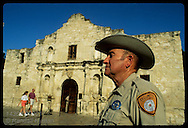 Ranger Jerry Rowe stands guard in front of Alamo on hot October day as tourists pass;San Antonio Texas