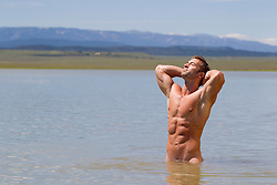 nude man soaking up the sun while standing in a lake in New Mexico