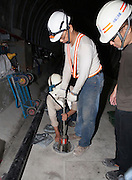 Workers fit a tool that uses an air compressor to raise the track bed during construction of a new MRT line.