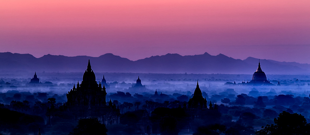 Morning Mystery: Silhouetted ancient ruins poke out from the morning mist and are strewn across the plains, Bagan Myanmar.