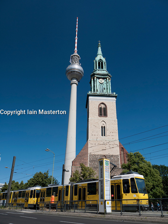 contrast between spire of old Marienkirche and the Fernsehturm or Television Tower in Alexanderplatz in Mitte Berlin Germany