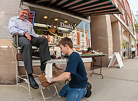 Senator Andrew Hosmer gets a shoeshine from Nathan Daubens of Daub's Cobbler Shop during Laconia Main Street's Sidewalk Sale on Wednesday afternoon.  (Karen Bobotas/for the Laconia Daily Sun)
