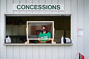 21 JULY 2020 - COLFAX, IOWA:A concessionaire wearing a mask and protected by a plexiglass shield at the Jasper County Fair in Colfax, about 30 miles east of Des Moines. Summer is county fair season in Iowa. Most of Iowa's 99 counties host their county fairs before the Iowa State Fair. In 2020, because of the COVID-19 (Coronavirus) pandemic, many county fairs were cancelled, or scaled back to concentrate on 4H livestock judging. The Iowa State Fair was cancelled completely. The Jasper County Fair cancelled most events and focused on just the 4H contests.            PHOTO BY JACK KURTZ