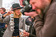 """Portland, Oregon, USA. 26 FEB, 2018. The photographer Leah Nash in hat helps in destroying the photographer Robert Frank's work printed on newsprint at Blue Sky Gallery in Portland, Oregon, USA. The work was destroyed in a """"Destruction Dance"""" performance defacing the photographs with ink and mutilation with scissors, knives and even ice skates  at the end of it's run. The destruction was Frank's protest regarding today's greed in the global art market."""