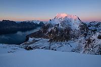 Himmeltindan mountain peaks rising over Uttakleiv village catch last sunlight, Vestvågøy, Lofoten Islands, Norway