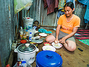 05 SEPTEMBER 2013 - BANGKOK, THAILAND:  A Cambodian woman makes som-tam (papaya salad) in her corrugated metal dormitory room after her shift at the construction site of a new high rise apartment / condominium building on Soi 22 Sukhumvit Rd in Bangkok. The workers live in the corrugated metal dorms on the site. Most of the workers at the site are Cambodian immigrants.             PHOTO BY JACK KURTZ
