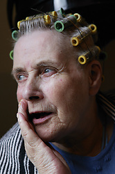 Elderly woman in the hairdressers wearing curlers,