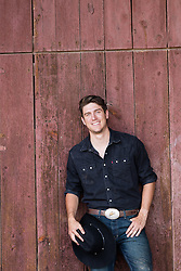 handsome cowboy against a barn smiling