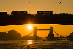 © Licensed to London News Pictures. 10/10/2018. London, UK.  Sunrise behind Tower Bridge on the River Thames as traffic passes on London Bridge during warm and sunny weather this morning.  Photo credit: Vickie Flores/LNP