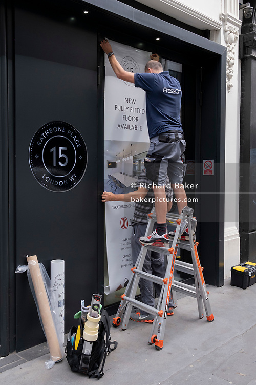 Two contractors with the PressOn company use teamwork expertise to attach an adhesive poster to the exterior of premises on Rathbone Place, on 12th July 2021, in London, England.