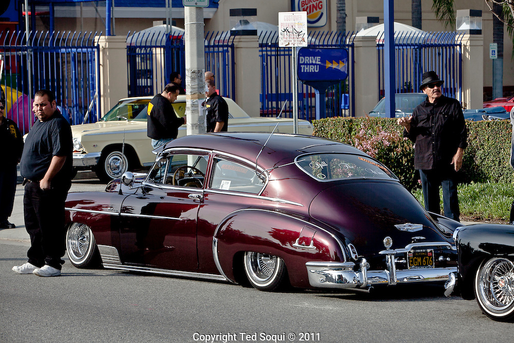 """Funeral procession for lowrider pioneer and founding member of the Imperials Car Club, Jesse Valadez..Valadez's  lowrider, """"Gypsy Rose"""" a 1964 Chevy Impala with painted roses on each side and a bright pink interior, is considered to be the world's most famous lowrider by many car enthusiast. It was featured on the sitcom """"Chico and the Man,"""" and took two and a half years to complete. .Hundreds of lowriders from the Imperial and fellow car clubs led a procession through East L.A., with the """"Gypsy Rose"""" leading on a flat bed truck."""
