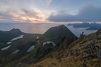 Female hiker overlooks village of Myrland and surrounding moutain landscape from Middagstind, Flakstadøy, Lofoten Islands, Norway