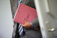 DEU, Deutschland, Germany, Berlin, 14.08.2013:<br />Ein Mitarbeiter der Senatsverwaltung für Wirtschaft, Technologie und Forschung hält eine Akte mit dem Vermerk Eilt in der Hand.