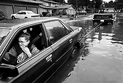 Flood water begins to soak Stacy Hafner's toes as passing motorists Kevin Scheuffele, right, and Troy Long, inside the truck, help pull her stalled car out of an intersection in Renton that filled when storm drains overflowed yesterday.: THE WATER BEGINS TO SOAK STACY HAFNER'S TOES AS KEVIN SCHEUFFELE, RIGHT, AND TROY LONG, INSIDE PICKUP, RESCUE HER STALLED CAR IN RENTON. : WASHINGTON STATE.