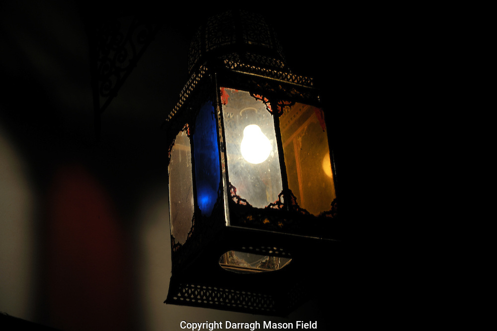 A Moroccan lamp illuminated by a single bulb