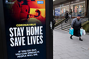 HM Government, and NHS advice boards for people to not go out, minimise contact, stay at home and save lives during the third national coronavirus lockdown in Birmingham city centre, which is deserted apart from a few people on 12th January 2021 in Birmingham, United Kingdom. Following the recent surge in cases including the new variant of Covid-19, this nationwide lockdown, which is an effective Tier Five, came into operation yesterday, with all citizens to follow the message to stay at home, protect the NHS and save lives.