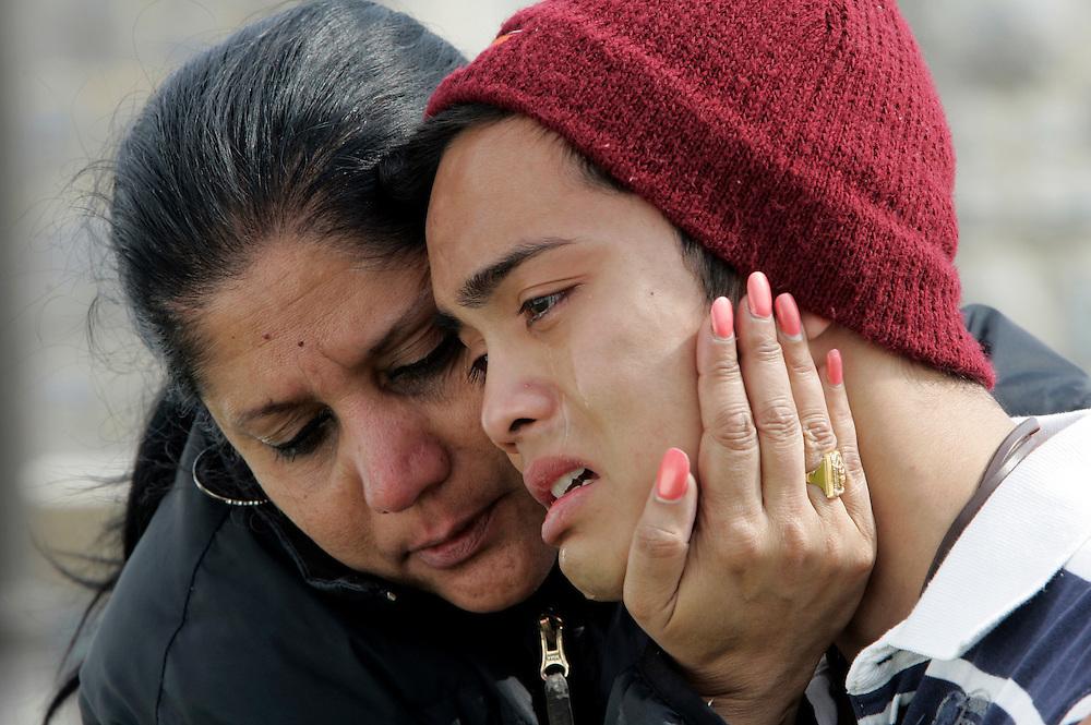 Ramon Cruz (R), a freshman at Virginia Tech weeps at a memorial to the shooting victims at Virginia Tech in Blacksburg, Virginia April 18, 2007. Comforting Cruz is Gigi Giridhar (L) the mother of Cruz's best friend Sanjay also a freshman at the school.  REUTERS/Rick Wilking (UNITED STATES)