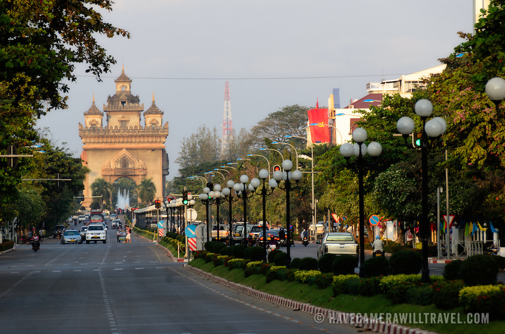 """View down Avenue Lane Xang in Vientiane, Laos, in front of the Presidential Palace. At left, in the distance is Patuxai (Victory Gate or Gate of Triumph), a war memorial. It's also known colloquially as the """"vertical runway"""" because it's made from concrete supplied by American aid to build an airport that was never finished. It is also sometimes transliterated as Patuxai, Patuxay, Patousai and Patusai"""