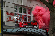 Activists from Palestine Action human rights group sprayed red paint and used red flares to scale the roof of Elbit System HQ at 77 Kingsway in central London on Friday morning, Aug 6, 2021. Activists argue that the weapons being manufactured from Elbit Systems are being used in indiscriminate attacks against the Palestinians in Gaza Strip. Two activists remain to occupy the building's entry. (VX Photo/ Vudi Xhymshiti)