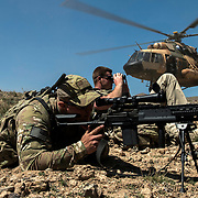 A Czech Republic Joint Terminal Attack controller from the Train, Advise, Assist Command - Air, guides a Afghan Air Force Mi-17 onto the landing zone, while US Army Soldiers provide security, Apr 9, 2015 at a training range outside of Kabul, Afghanistan. The AAF demonstrated the capabilities of the MD-530F's two FN M3P .50 Cal machine guns to local media and Afghan military leaders. (U.S. Air Force Photo by Staff Sgt. Perry Aston/Released)