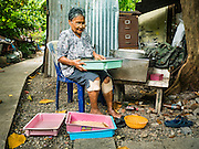 30 JULY 2016 - BANGKOK, THAILAND:  A woman packages bird food she sells in the Pom Makahan Fort slum. Residents of the slum have been told they must leave the fort and that their community will be torn down. Mahakan Fort was built in 1783 during the reign of Siamese King Rama I. It was one of 14 fortresses designed to protect Bangkok from foreign invaders. Only of two are remaining, the others have been torn down. A community developed in the fort when people started building houses and moving into it during the reign of King Rama V (1868-1910). The land was expropriated by Bangkok city government in 1992, but the people living in the fort refused to move. In 2004 courts ruled against the residents and said the city could take the land. Eviction notices have been posted in the community and people given until April 30 to leave, but most residents have refused to move. Residents think Bangkok city officials will start evictions around August 15, but there has not been any official word from the city.     PHOTO BY JACK KURTZ