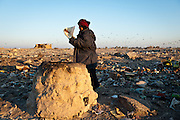 A woman bakes bread in a mudbrick oven in the midst of a garbage dump where a community of displaced Shia from southern Iraq has taken refuge.