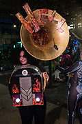 New York, NY - 31 October 2019. the annual Greenwich Village Halloween Parade along Manhattan's 6th Avenue. A woman costumed as a jukebox / sousaphone, with HELL lettered on the bel of the instrument, and a rat running out of it.