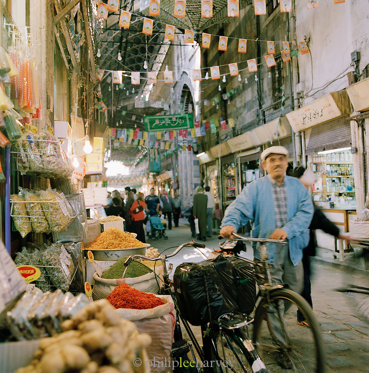 A man walks his bicycle down a narrow passage in one of the souq streets of Damascus, Syria