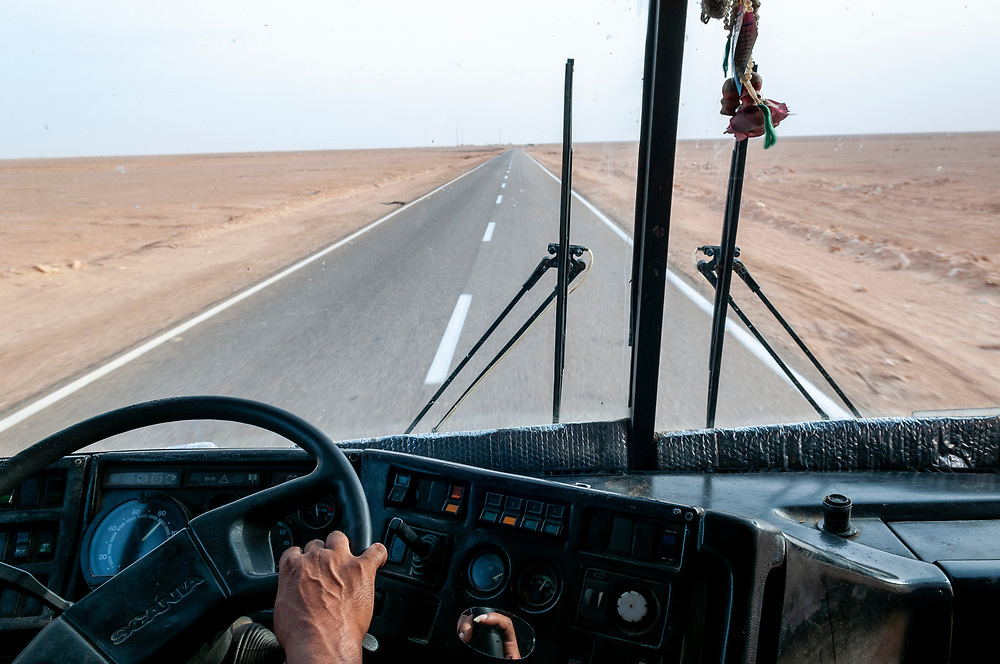 A bus driver at the wheel moves down the desert highway from Marsa Matruh to Siwa in Egypt. (May 2010)