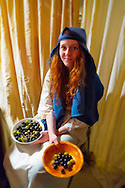 Garden City, New York, USA. December 6, 2013. At Olive Stall, young woman holds bowls of green and black olives, t A Night in Bethlehem, where visitors experience what it might have been like the night Jesus was born. Families visit different shops and participate in projects. Finally the children and adults experience the nativity scene at the manger, with Mary, Joseph, and baby Jesus, on the first Christmas. This free annual Advent event is December 6, 7, and 8, at the Lutheran Church of the Resurrection, on Long Island.