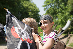 Portrait of a girl dressed up as a pirate holding pirate flag in adventure playground, Bavaria, Germany