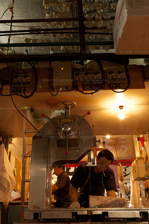 A wholesaler uses a saw to cut a piece of frozen tuna into smaller pieces at Tsukiji wholesale fish market in Tokyo, Japan July 15th 2008