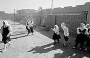 School girls in full traditional clothing playing tag in a schoolyard