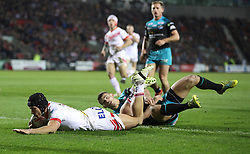 St Helens Saints' Jonny Lomax goes over for a try past Leeds Rhinos Stevie Ward, during the Betfred Super League match at the Totally Wicked Stadium, St Helens.