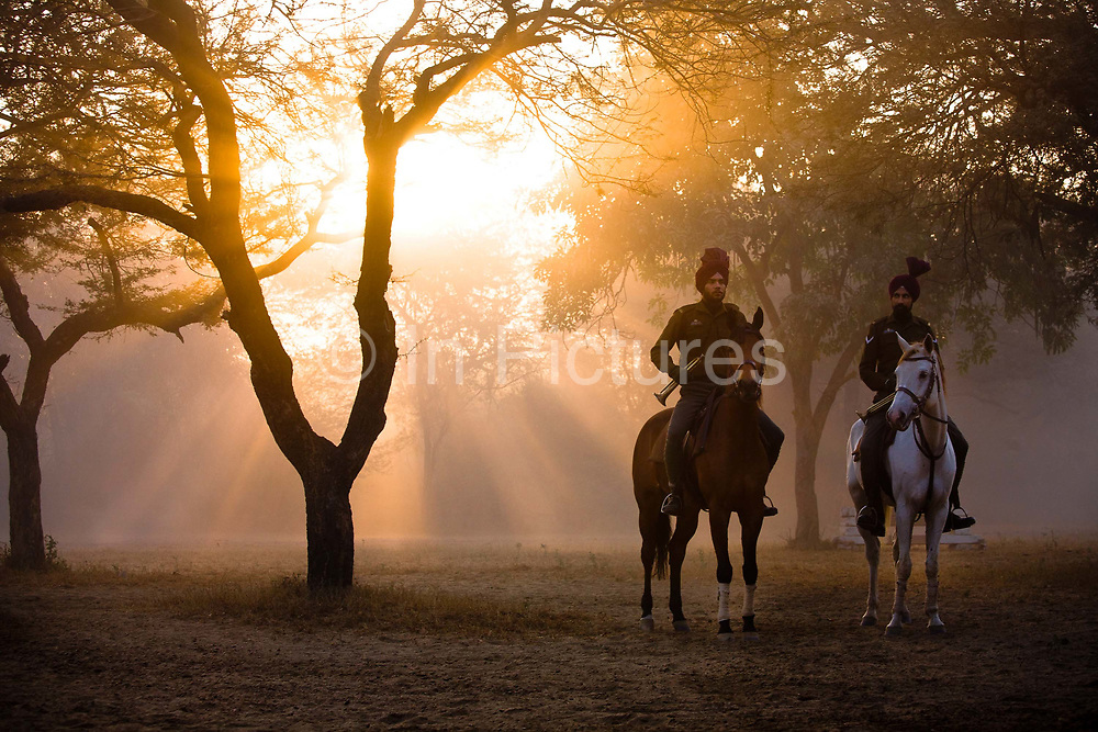 Presidential Bodyguard soldiers in early morning dust and mist filled horsemanship practice, consisting of jumping, daredevil riding and other such activities at the PBG's training grounds. This a regular activity as it requires the riders to perfect their horse riding skills and maneuvers for their official duties at ceremonial events.  The PBG is the Indian Army's preeminent regiment founded in 1773 during the British occupation, this handpicked unit began with a mere 50 men and today stands at 160 soldiers plus 50 support staff. It has a dual role, both as a ceremonial guard for the President of India, with all its finery at important state functions, as well as an elite operational unit for the Indian Army which has seen action in many battle fronts, in particular the on going disputed region of Kashmir.